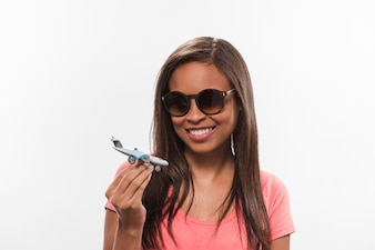 Portrait of a happy girl in sunglasses holding airplane