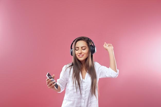 Портрет счастливой девушки, слушающей музыку в беспроводных наушниках со смартфона
