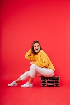 Портрет счастливая девушка сидит на бумбокс