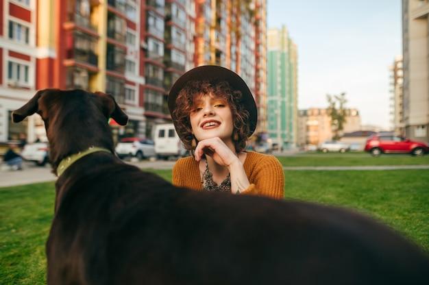 Портрет счастливой девушки с собакой на лужайке во дворе