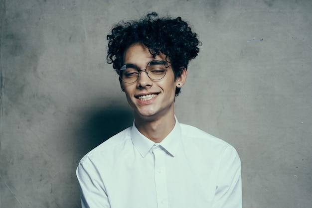 眼鏡をかけた幸せな男の肖像巻き毛の白いシャツの写真撮影モデル