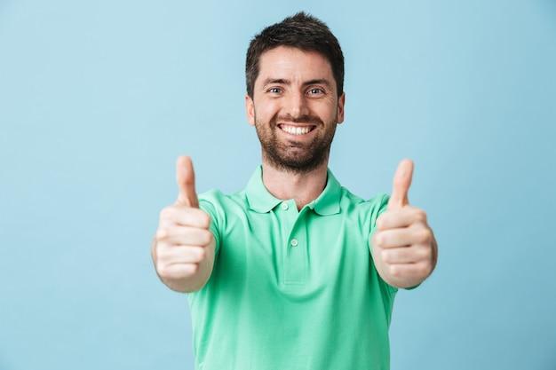 Портрет счастливого красивого бородатого мужчины в повседневной одежде, стоящего изолированно над синей стеной, показывает палец вверх