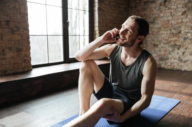 Портрет счастливого здорового спортсмена говоря на мобильном телефоне