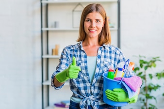 Portrait of a happy housemaid with bucket of cleaning equipments gesturing thumbs up