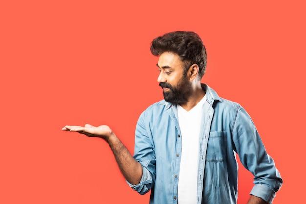 빨간색 복사 공간에서 멀리 손가락을 가리키는 행복 인도 수염 젊은 남자의 초상화