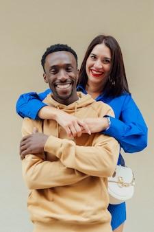 スタジオの黄色の背景にカジュアルな服を着た幸せな異人種間のカップルの肖像画。ヨーロッパの外観の若いブルネットは彼女のアフリカ系アメリカ人のボーイフレンドを抱擁します