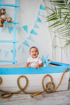 木製のボートに座っている幸せな子供の男の子の肖像画