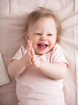 그의 얼굴에 재미 있는 표정으로 행복 웃는 아기의 초상화. 파란 눈을 가진 작고 아름다운 소녀가 밝게 웃고 첫 번째 이빨이 보입니다.