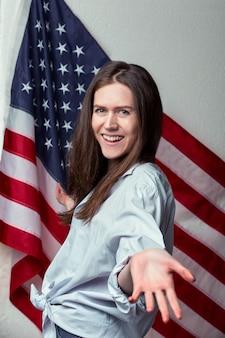 アメリカの国旗の表面に幸せな笑う美しい若い女性の肖像画