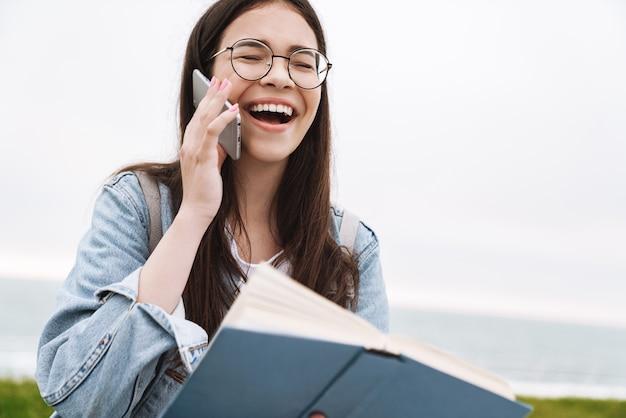 Портрет счастливого смеха эмоционального молодого симпатичного студента женщины в очках, идущего на открытом воздухе, чтения книги, говорящего по мобильному телефону.