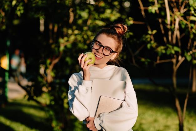 バックライトで歩く収集された髪を持つ幸せな笑う若い女性の肖像画