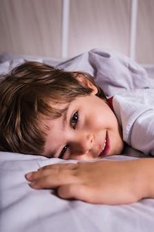 寝室のベッドに横たわっているパジャマを着た幸せな少年の肖像画