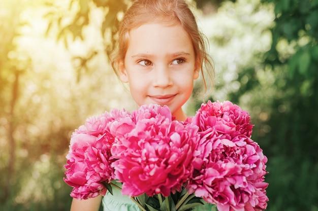 Портрет счастливой маленькой кавказской семилетней девочки, держащей в руках букет розовых пионов Premium Фотографии