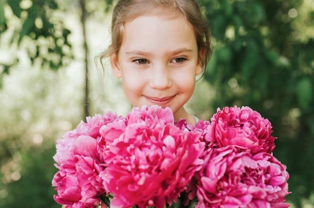 Портрет счастливой маленькой кавказской семилетней девочки, держащей в руках букет розовых пионов