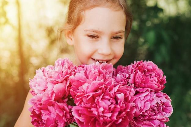 Портрет счастливой маленькой кавказской семилетней девочки, держащей в руках, пахнущей и наслаждающейся Premium Фотографии