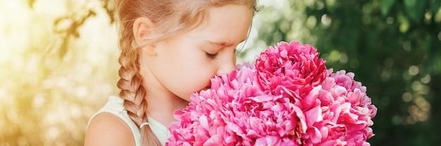 Портрет счастливой маленькой кавказской семилетней девочки, держащей в руках, пахнущей и наслаждающейся