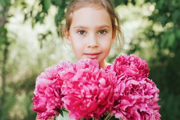 Портрет счастливой маленькой девочки держит в руках букет цветущих розовых пионов