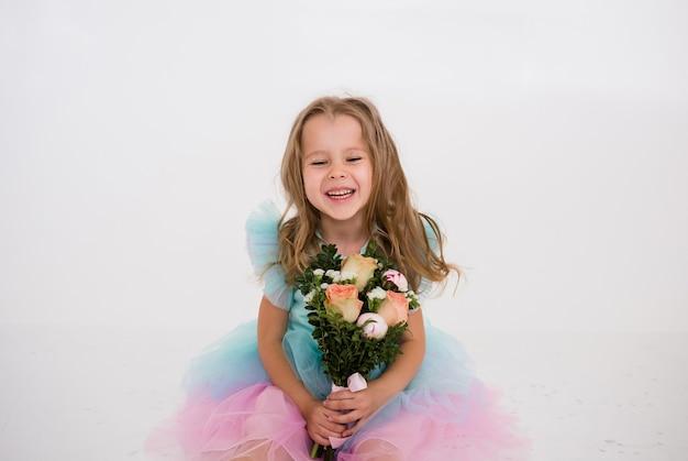 テキストの場所と白い背景に新鮮な花の花束を保持しているお祝いのドレスを着た幸せな少女の肖像画