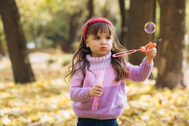 Портрет счастливой маленькой девочки, играющей с мыльными пузырями из осенних листьев в парке