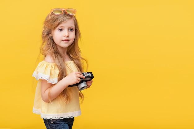 Портрет счастливой маленькой девочки с длинными волосами с ретро-камерой в руках
