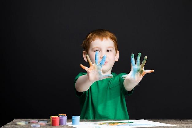 행복한 redhaired 소년의 초상화는 손의 도움으로 종이에 그립니다