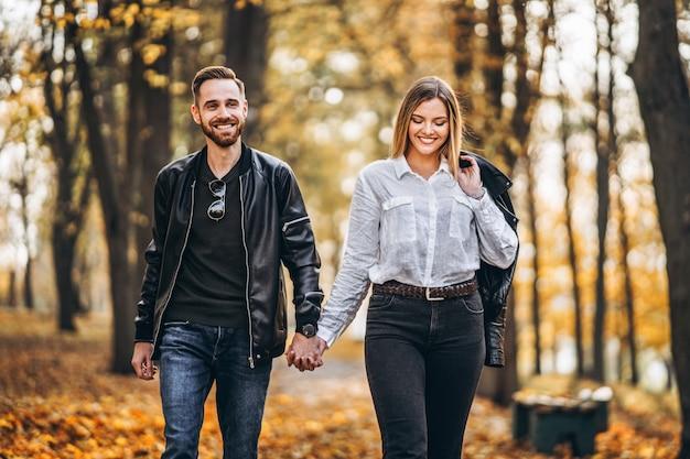 秋の公園で屋外を歩く幸せな愛情のあるカップルの肖像画