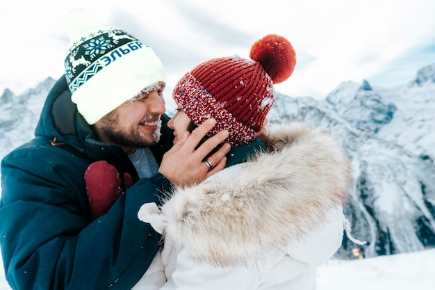 Портрет счастливого мужчины и женщины в горах крупным планом. муж и жена обнимаются на отдыхе зимой.