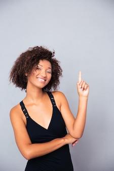 Портрет счастливого человека, указывающего пальцем вверх над серой стеной