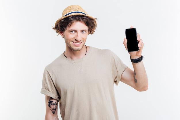 白い背景で隔離の空白の画面でスマートフォンを提示する幸せな男の肖像画