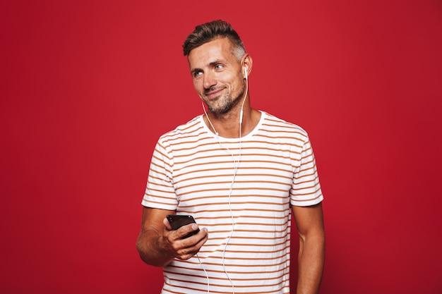 赤の上に立っている幸せな男の肖像画