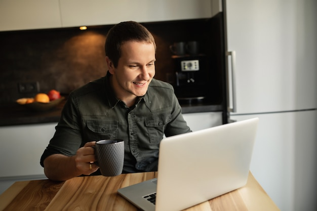 家で働く幸せな男の肖像。室内のラップトップに取り組んでいるキッチンルームで一杯のコーヒーを机に座っている男