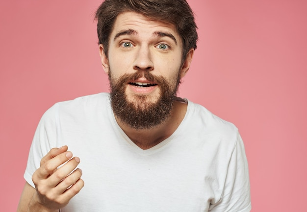 白いtシャツのピンクのひげを持つ幸せな男の肖像画。