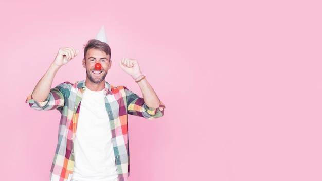 분홍색 배경에 광대 코를 가진 행복 한 남자의 초상