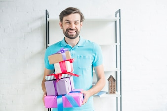 Portrait of a happy man with stacked valentine gifts
