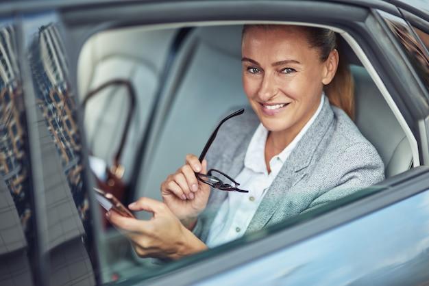 차 뒷좌석에 앉아 스마트폰을 사용하는 행복한 성숙한 비즈니스 여성의 초상화