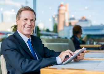 Portrait of a happy mature businessman using digital tablet in restaurant