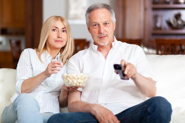 一緒にテレビを見ている彼らの家で幸せな成熟したカップルの肖像画