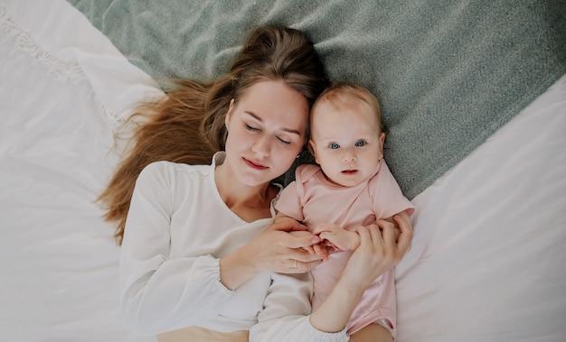 幸せな母と寝室のベッドに横たわっている赤ん坊の娘の肖像画