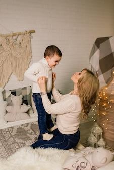幸せな母親と愛らしい赤ちゃんのポートレートは、クリスマスを祝います。年末年始