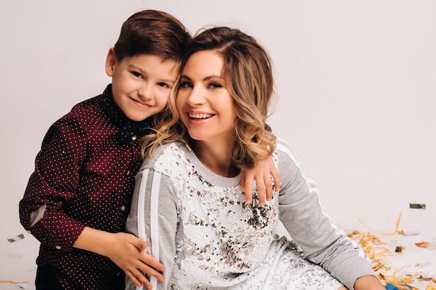 Портрет счастливой матери и сына на белом фоне.