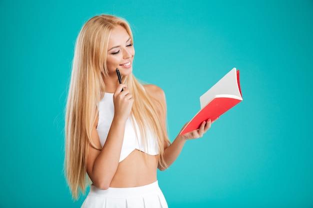 Портрет счастливой задумчивой женщины, делающей заметки в блокноте, изолированном на синем фоне