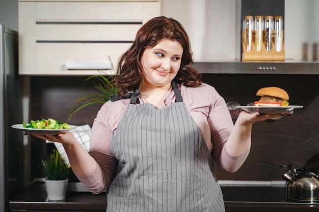 キッチンでハンバーガーとプレートとサラダとプレートを保持している幸せなプラスサイズの女性の肖像画。健康的な栄養とジャンクフードのどちらかを選択するという概念