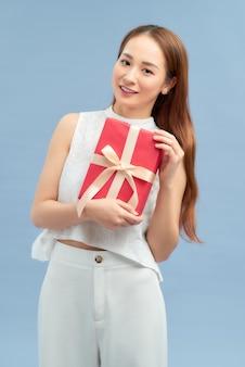 明るい青色の背景の上に立っている間プレゼントボックスを保持している幸せなきれいなアジアの女性の肖像画