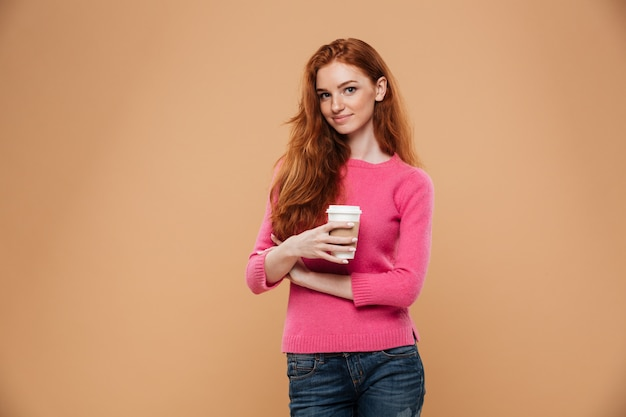 Портрет счастливого довольно рыжая девушка держит чашку кофе