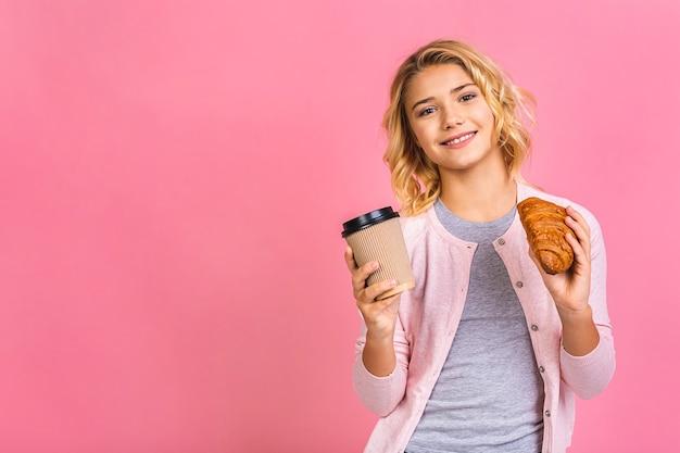 Портрет счастливой красивой девочки подростка ест круассан и пьет кофе