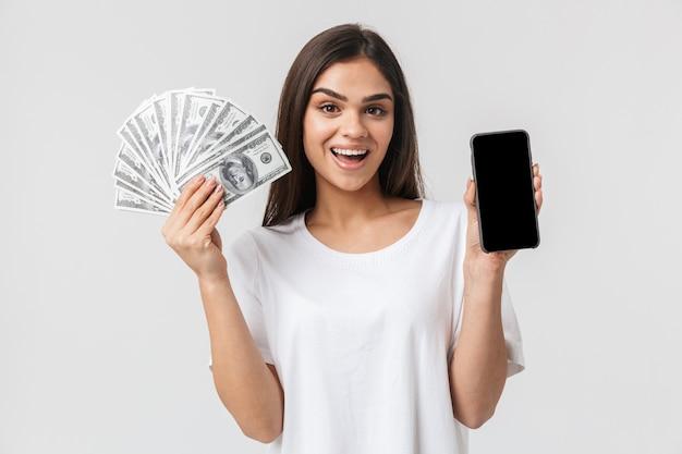 빈 화면 휴대 전화를 보여주는 돈 지폐를 보여주는 흰색 절연 캐주얼 옷을 입고 행복 꽤 젊은 여자의 초상화
