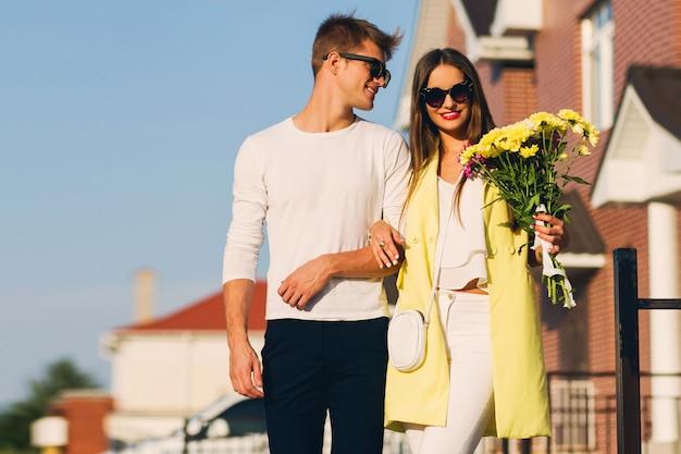 夕方にはヨーロッパの都市で屋外を受け入れる幸せなロマンチックなカップルの肖像画。花を持って若いきれいな女性。恋愛のカップル。