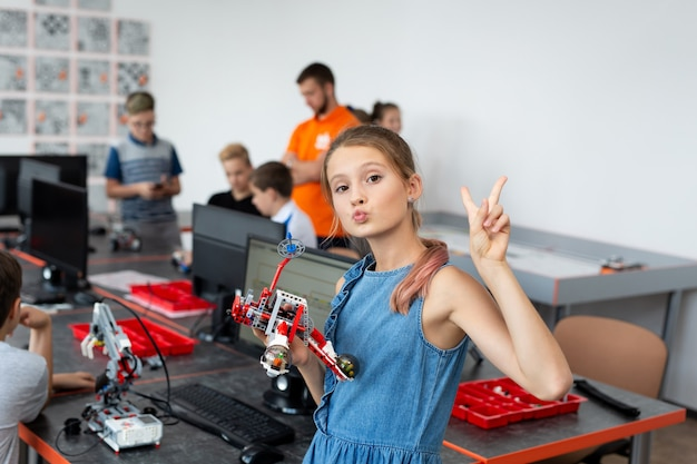 Портрет счастливой школьницы в классе робототехники, она держит робота, собранного из пластиковых деталей, запрограммированных на компьютере