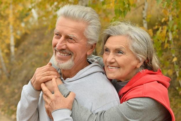 秋の公園で幸せな年配のカップルの肖像画