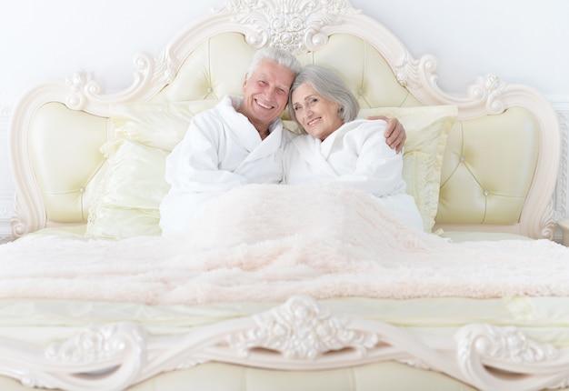 Портрет счастливой старшей пары в постели